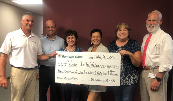 TAV staff posing with large check